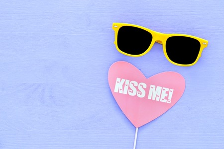 image of cute yellow black sunglasses and heart sign over purple wooden background