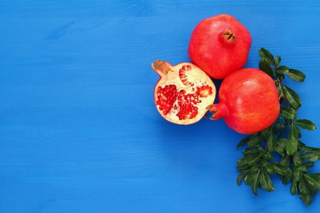 Rosh hashanah (jewesh New Year holiday) concept - pomegranate over wooden blue background. Traditional symbol