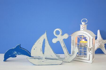 Magical lantern with candle light and wooden boat on the shelf. Nautical concept. Stock Photo