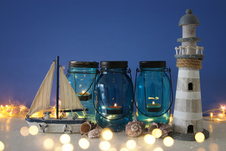 Magical mason jars whith candle light and wooden boat on the shelf. Nautical concept.
