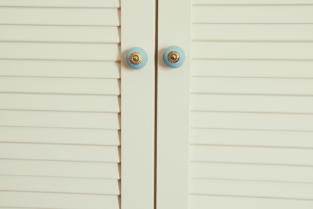 centered: vintage white closet with ornate handles on the doors. interior decor background.