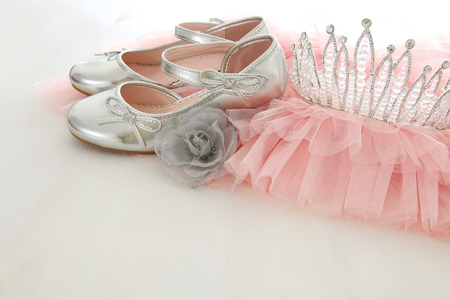 Vintage tulle pink chiffon dress, crown and silver shoes on wooden white floor. Wedding, bridesmaid and girls party concept
