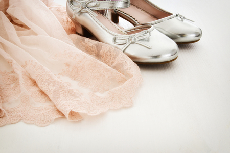 silver background: Vintage tulle pink chiffon dress and silver shoes on wooden white floor. Wedding, bridesmaid and girls party concept
