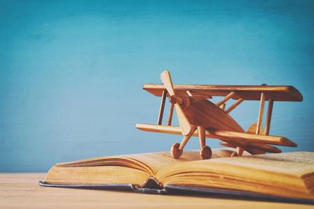 Speelgoedvliegtuig en het open boek op houten lijst.