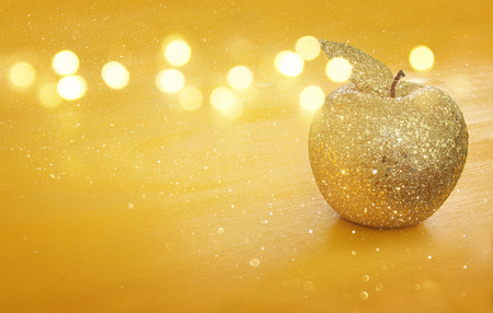 Rosh hashanah (jewish New Year holiday) concept. Decorative gold glitter apple.