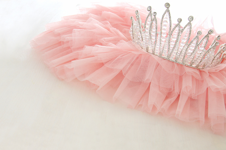 Vintage tulle pink chiffon dress and diamond tiara on wooden white table. Wedding and girls party concept.