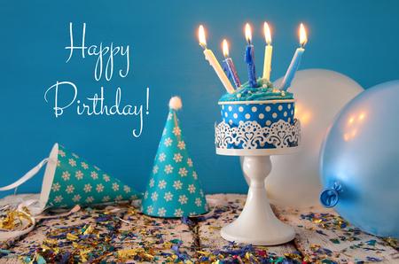 Verjaardagsconcept met cupcake en kaarsen op houten tafel.