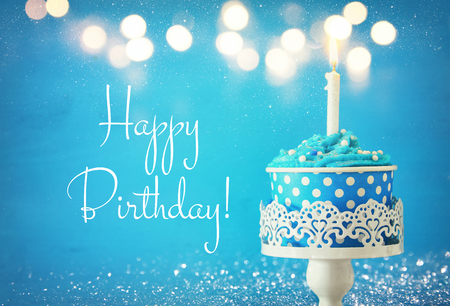 Verjaardagsconcept met cupcake en kaarsen op houten lijst