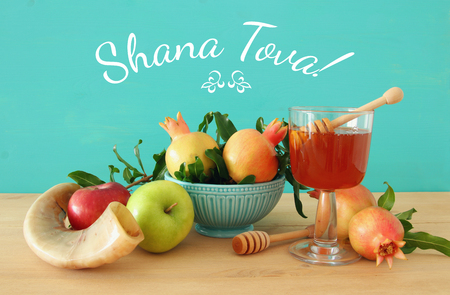 Rosh hashanah (jewish New Year holiday) concept. Traditional symbols. Text SHANA TOVA means HAPPY NEW YEAR in hebrew
