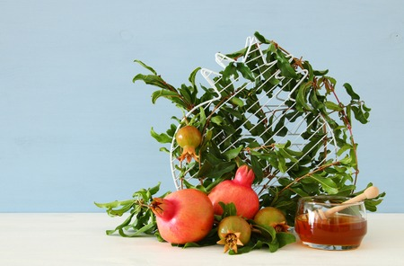 Rosh hashanah (jewesh New Year holiday) concept - pomegranate over wooden background. Traditional symbol