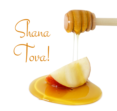 honey dripping on apple isolated on a white. Rosh hashanah (jewish New Year holiday) concept. Traditional symbol. Text SHANA TOVA means HAPPY NEW YEAR in hebrew