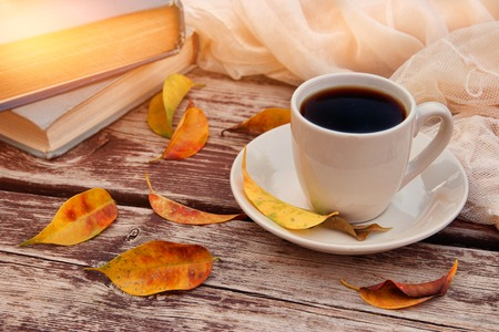 image of coffee cup over wooden table and autumn leaves outdoor in the park. Stock Photo