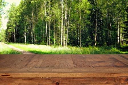 木製テーブル前に緑の森木風景の背景の画像。製品の展示やプレゼンテーションの