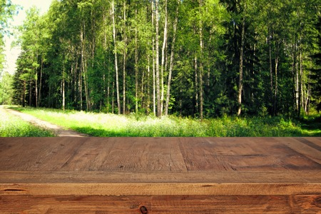 image of wooden table in front green forest trees landscape background. for product display and presentation