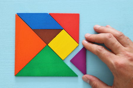 man's: mans hand holding a missing piece in a square tangram puzzle, over wooden table.