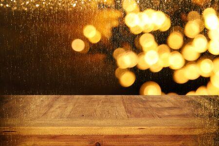 mesa de tablero de madera en frente de Navidad luces cálida guirnalda de oro sobre fondo de madera rústica.