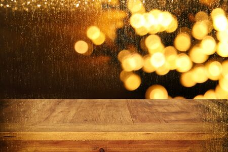 wood board table in front of Christmas warm gold garland lights on wooden rustic background.