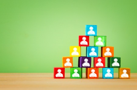 image of a wood blocks pyramid with people icons over wooden table , human resources and management concept