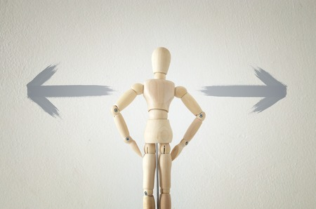 image of wooden person standing with his back in front of textured background full of arrows pointing in different directions. decision and strategy plan concept