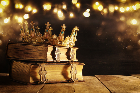 low key image of beautiful queenking crown on old book. vintage filtered. fantasy medieval period