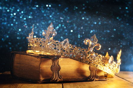 low key image of beautiful queen/king crown on old book. vintage filtered. fantasy medieval period Foto de archivo