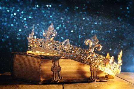 Immagine bassa chiave della bella regina / re corona sul vecchio libro. Annata filtrata. Periodo fantasy medievale