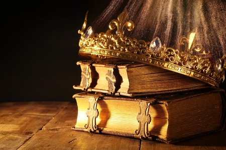 low key image of beautiful queenking crown on old books. vintage filtered. fantasy medieval period