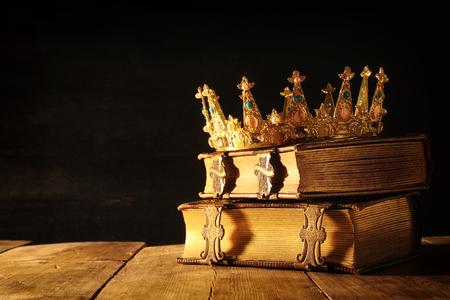low key afbeelding van mooie koningin  koning kroon op oude boeken. vintage gefilterd. fantasie middeleeuwse periode