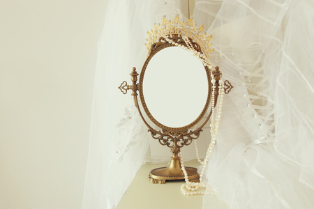 Old vintage oval mirror and beautiful white wedding dress and veil on chair. Copy space for mock up, montage or design layout.