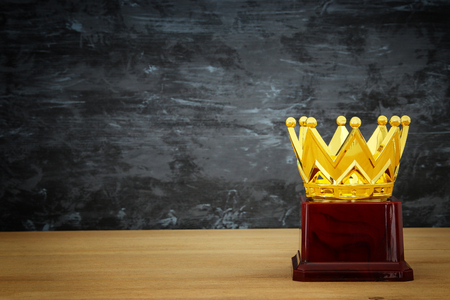 image of golden crown award over wooden table.
