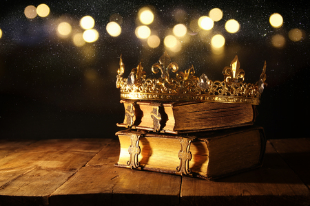 low key image of beautiful queen/king crown on old books. vintage filtered. fantasy medieval period 写真素材