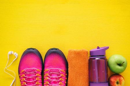 カラフルな背景の上の水、タオル、女性のピンクのスポーツ靴のボトルとフィットネスの概念。 写真素材