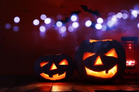 Calabaza de Halloween en la mesa de madera delante del fondo oscuro fantasmagórico. Jack o linterna.