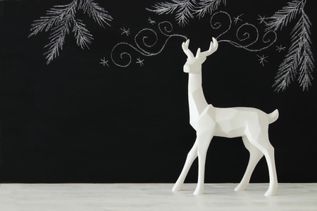 White reindeer on wooden table over chalkboard background whith hand drawn chalk illustrations