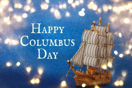 Columbus day concept with old ship over blue glitter background.