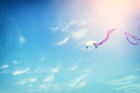 Colorful kite flying in the blue sky through the clouds.