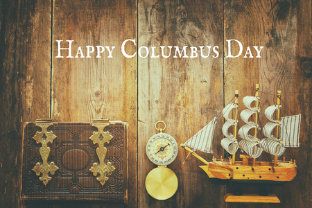 Columbus day concept with old ship over wooden background