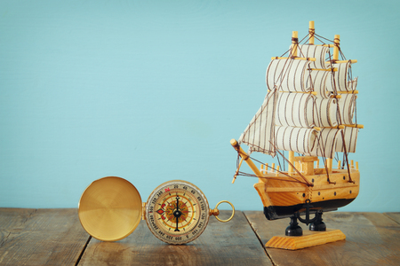 Columbus day concept with old ship over wooden background.