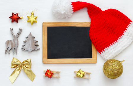 Image of cute knitted santa hat and blackboard next to christmas decorations Stock Photo
