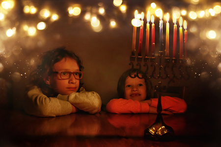 Low key image of jewish holiday Hanukkah background with two cute kids looking at menorah (traditional candelabra) and burning candles.