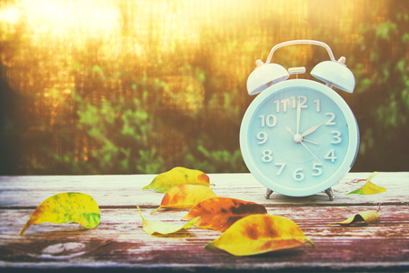 Image of autumn Time Change. Fall back concept. Dry leaves and vintage alarm Clock on wooden table outdoors at afternoon Stock Photo