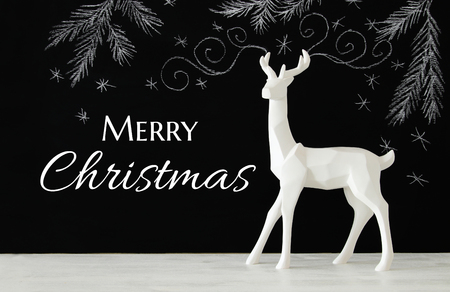 decorating: White reindeer on wooden table over chalkboard background whith hand drawn chalk illustrations.