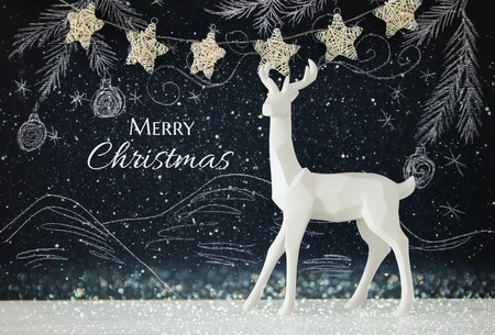 decorating: White reindeer on wooden table over chalkboard background whith hand drawn chalk illustrations