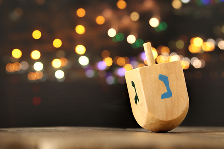 Image of jewish holiday Hanukkah with wooden dreidel (spinning top) and gold lights on the table Zdjęcie Seryjne