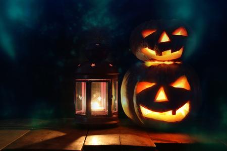 Halloween Pumpkins on wooden table in front of spooky dark background. Jack o lantern