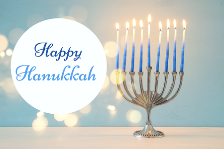 image of jewish holiday Hanukkah background with traditional menorah (traditional candelabra) and burning candles.