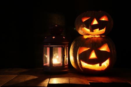 Halloween Pumpkin on wooden table in front of spooky dark background. Jack o lantern. Stock Photo