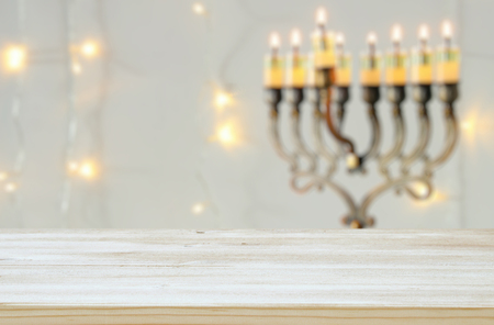 Empty wooden table in front of jewish holiday Hanukkah background with menorah (traditional candelabra). For product display