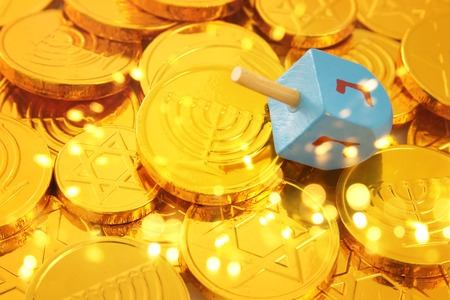 Image of jewish holiday Hanukkah with wooden dreidels (spinning top) and gold chocolate coins.