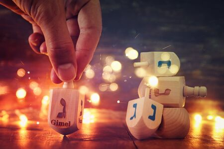 Image of jewish holiday Hanukkah with wooden dreidels colection (spinning top) and gold garland lights on the table. Stock Photo